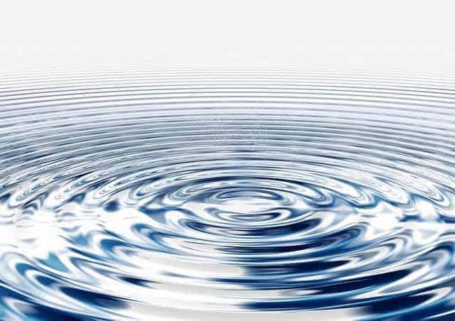 Eine Wasseroberfläche bildet Wellen der Entspannung aus dem Zentrum heraus.