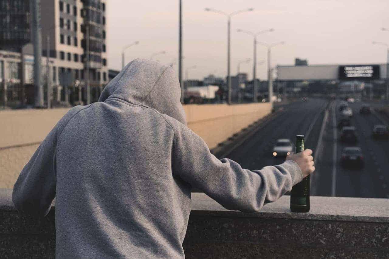 Entspannung durch Alkohol oder Drogen führt zu gesundheitlichen Problemen. Hier symbolisiert durch einen Mann, der auf einer Brücke steht mit einer Flasche Alkohol.