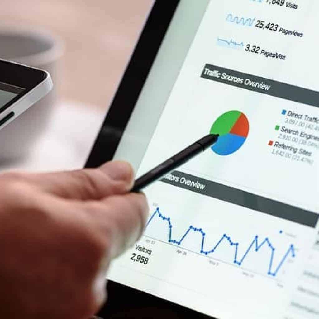 hand die auf eine Analyse des Google Ranking am Computer zeigt.