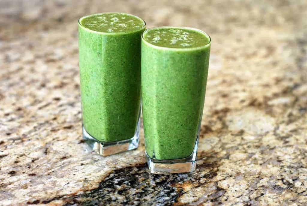 Zwei grüner Smoothies im Glas auf einer Marmorplatte. Die starke Farbe stammt vom Chlorophyll her - wobei diese Substanz selbst schon unterstützend auf die Gesundheit wirkt.