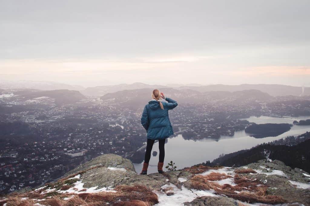 Blonde Frau, welche weit in die Ferne schaut, um sich Ziele zu definieren, die sie erreichen möchte. Im Hintergrund sind Hügel und ein See zu sehen.
