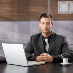 Ein Mann in sitzender Meditation im Büro vor einem Notebook.